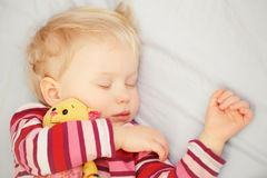 Cute sleeping blond baby with toy Stock Photo