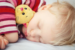 Cute sleeping blond baby with toy Royalty Free Stock Photography