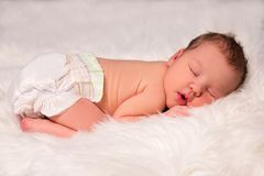 Cute sleeping newborn baby in diaper over white blanket. Cute sleeping newborn baby in diaper over white fur blanket Royalty Free Stock Photography