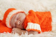 Cute sleeping newborn baby dressed in a knitted orange costume o Royalty Free Stock Image