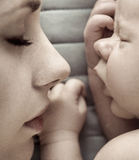 Cute sleeping newborn baby with his mother Stock Images