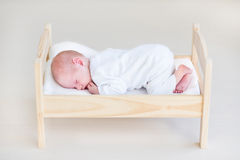 Cute sleeping newborn baby in a toy bed Stock Images