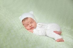 Cute sleeping newborn baby in white knitted fluffy kitten costume. Cute sleeping newborn baby in white knitted fluffy romper with kitten hat lies on the tummy on royalty free stock photos