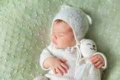 Cute sleeping newborn baby in white knitted fluffy kitten costume Stock Images