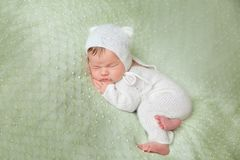 Cute sleeping newborn baby in white knitted fluffy kitten costume. Cute sleeping newborn baby in white knitted fluffy romper with kitten hat lies on the tummy on Stock Image