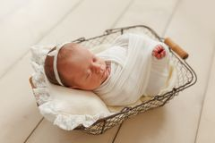 Cute sleeping newborn girl with a bandage on her head on a small stock image