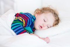 Cute sleeping toddler girl in a bed Stock Images
