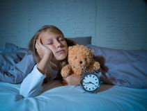Little Girl in bed awake at night yawning and feeling restless showing clock she can not sleep. Cute sleepless little girl lying in bed showing alarm clock stock image