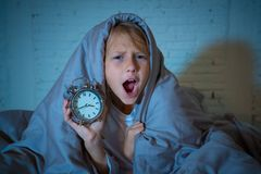 Little Girl in bed awake at night yawning and feeling restless showing clock she can not sleep. Cute sleepless little girl lying in bed showing alarm clock stock photo