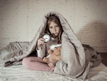 Little girl sitting on bed with teddy bear and alarm clock sleepless at night suffering insomnia stock photography