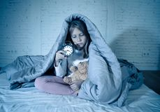 Little girl sitting on bed with teddy bear and alarm clock sleepless at night suffering insomnia royalty free stock photo