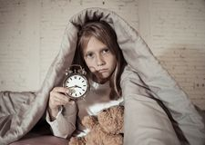 Little girl sitting on bed with teddy bear and alarm clock sleepless at night suffering insomnia royalty free stock images