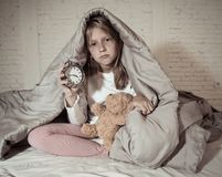Little girl sitting on bed with teddy bear and alarm clock sleepless at night feeling restless. Cute sleepless little girl sitting on bed looking sad and tired stock image
