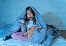 Little girl sitting on bed with teddy bear and alarm clock sleepless at night feeling restless. Cute sleepless little girl sitting on bed looking sad and tired stock photo