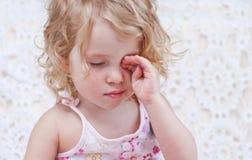 Cute sleepy baby girl. Hand rubs eyes royalty free stock photography