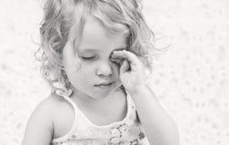 Cute sleepy baby girl. Hand rubs eyes ( black and white Stock Photos