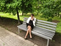 Cute Slender Woman In A Business Suit Sits On A Bench In The Park With A Laptop And Speaks By Phone. An Adult Girl In Glasses Royalty Free Stock Photo