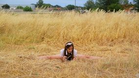 Cute slim girl with long hair in shorts and t-shirt makes twine and smiles on field with golden grass stock video