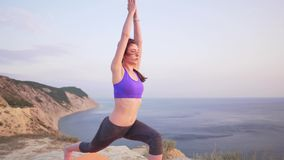 Cute slim girl tries to do yoga, falls and laughs. 4k stock footage