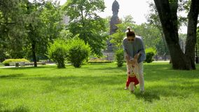 Cute slim mother helps her pretty  funny daughter to make first steps on green grass in pictorial city park stock footage