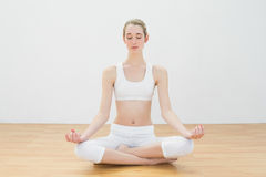 Cute slim woman meditating sitting in lotus position in sports hall Royalty Free Stock Photo