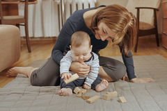 Cute small baby boy playing with wooden blocks royalty free stock photos