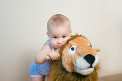 Cute small baby boy riding on the lion toy . Happy child emotions. Royalty Free Stock Photo