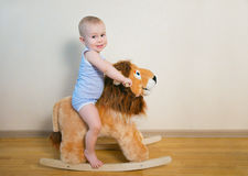 Cute small baby boy riding on the lion toy . Happy child emotions. Stock Photos