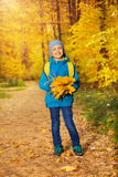 Cute small boy with bunch of yellow maple leaves Royalty Free Stock Photos
