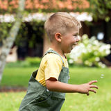Cute small boy chasing soap bubbles Stock Photography