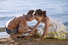 Cute small boy and girl playing in sand royalty free stock image