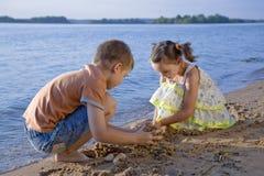 Cute small boy and girl on seashore. Cute small boy and girl playing in sand on seashore Stock Photo