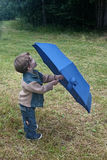 Cute small boy holding blue umbrella on green grass Stock Photos