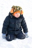 Cute small boy kneeling in winter snow Royalty Free Stock Image