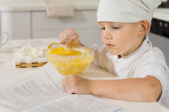 Cute small boy reading a recipe as he cooks Royalty Free Stock Photography