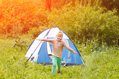Cute small boy runs happy near a tent on nature background . Stock Photography