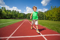 Cute small boy runs slowly on the marathon road Stock Photos