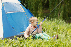 Cute small boy sits near a tent with a fishing rod in his hands. Stock Photo