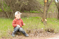 Cute small boy sitting on a stone waiting Stock Photography