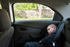 Cute small boy sleeping on back seat of car Royalty Free Stock Image