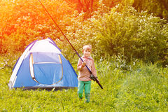 Cute small boy stand near a tent with a fishing rod in his hands. Stock Image