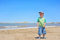 Cute small boy standing on the beach Stock Image