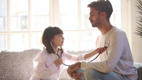 Cute child daughter holding stethoscope listening to father patient