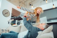 Cute small daughter with long hair looking amused. Amusement. Cute small daughter with long hair looking amused while playing with her father royalty free stock photo
