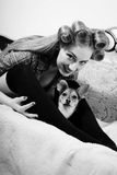 Cute small dog and beautiful blond young pinup. Closeup black and white portrait cute small dog and beautiful blond young pinup woman with blue eyes having fun Royalty Free Stock Images