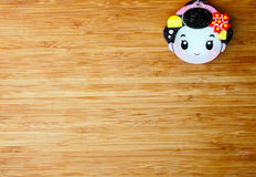 Cute small geisha face on wooden background Stock Photography