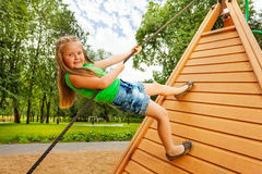 Cute small girl climbs on wooden construction Royalty Free Stock Images