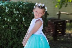 Cute small girl dressed in blue and white dress with a wreath of stock photos