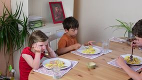 Cute small girl and her brothers eat the dinner. Children eat in the kitchen. Girl and boys in the kitchen. stock video footage