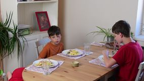 Cute small girl and her brothers eat the dinner. Children eat in the kitchen. Girl and boys in the kitchen. stock footage